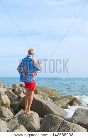 Senior Man looking at the sea wearing a blue Hawaii-shirt