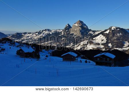 Village and holiday resort Stoos on a winter evening. View of Mt Mythen.