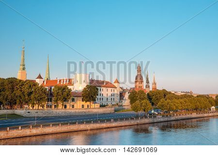 Scenic View To Promenad Of Daugava, In Riga, Latvia. Old Church Towers And Medieval Castle On Background. Seafront Named Ab Dambis. Evening  View With Blue Sky. Travel Destination. Urban View