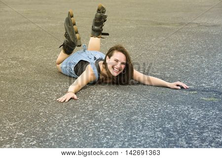 young woman with rollerblades lying on the street on her stomach and is laughing