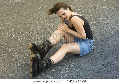 young woman with rollerblades sitting on the street in pain after accident