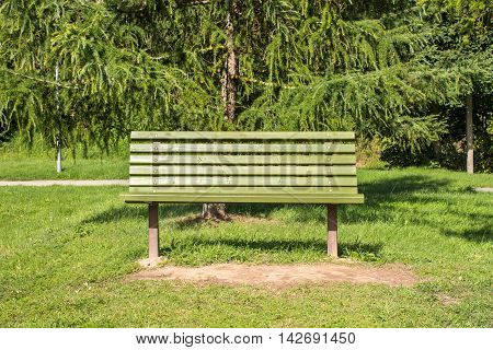 Empty wooden bench in a park for a hiker or casual walker to sit and rest.