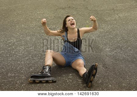 young woman with rollerblades sitting on asphalt and screaming
