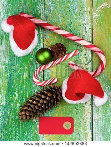 Christmas Decoration Concept with Small Santa Hats Striped Sweet Cane Fir Cones and Greeting Card closeup on Rustic Cracked background