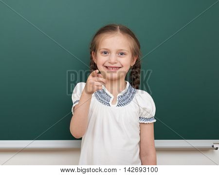school student girl posing at the clean blackboard, grimacing and emotions, dressed in a black suit, education concept, studio photo