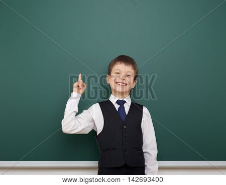 school student boy posing at the clean blackboard, show finger up and point, grimacing and emotions, dressed in a black suit, education concept, studio photo