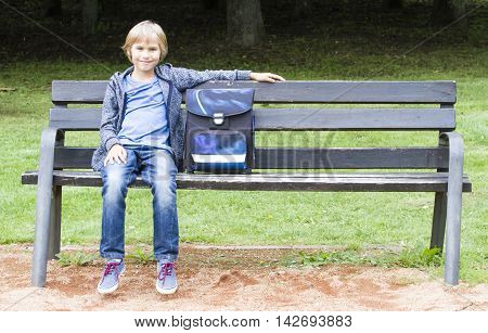 Smiling boy sitting on a wooden bench with his backpack. Education, school, lifestyle, people concept