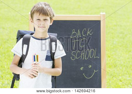 Little schoolboy with pens and backpack against the blackboard. Education, Back to school concept