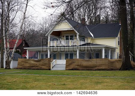 WEQUETONSING, MICHIGAN / UNITED STATES - DECEMBER 22, 2015: An elegant yellow Victorian home with a wraparound front porch and a balcony  in Wequetonsing.