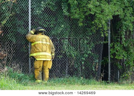 Firefighter Peering Through Fence