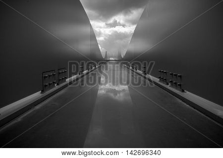 Contemporary black and white architecture object with rounded lines and dramatic cloudy sky. Reflection of clouds on steel constructin that looks like spaceship board.
