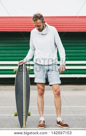 Hipster young man standing with the longboard at the stadium