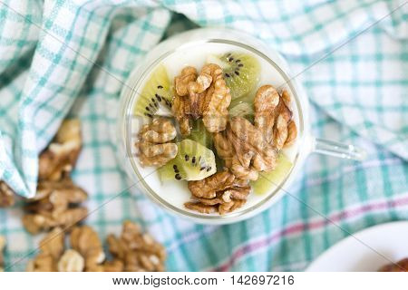 Glass With Plain Yogurt With Kiwi And Nuts