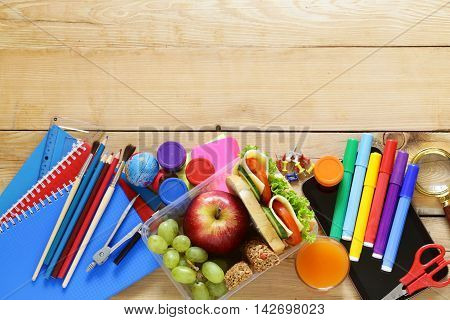 school stationery and lunch box with apple, grapes and sandwich