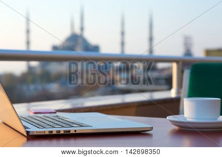Breakfast Table of travelling Hipster with Laptop and Telephone Coffee Mug and Istanbul attraction Mosque on blurred Background