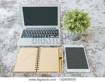 Closeup brown note book brown pen computer notebook tablet and artificial plant on gray fabric capet textured background