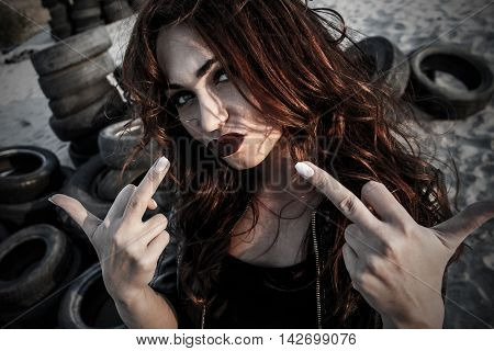 Disheveled redhead woman showing a finger signs
