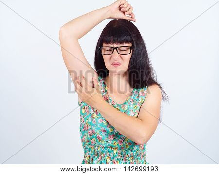 Unhappy Young Woman With Glasses Scratching Armpit.
