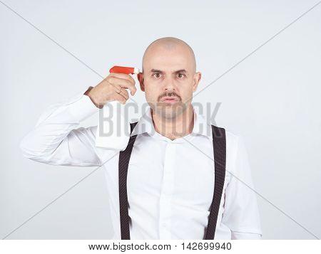 Bald Man Holding A Spray Bottle Near The Temple.