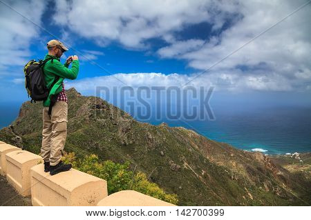 a tourist man taking the landscape photograph using his mobile smartphone