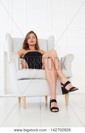 A fantastic model with red sweet lips and in a black sharp dress with black shoes is sitting on the armchair. Women in the black dress always know what they want from life