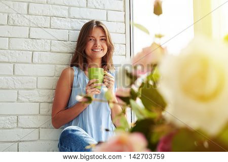 A charming young girl is very pleased while dreaming about something sitting on the windowsill and drinking a cup of aroma coffee