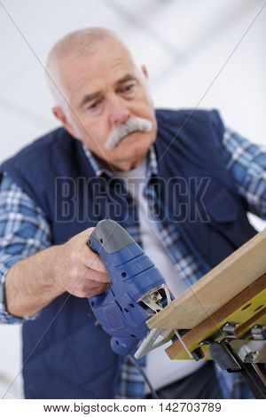 senior carpenter drilling hole in wood plank in his workshop
