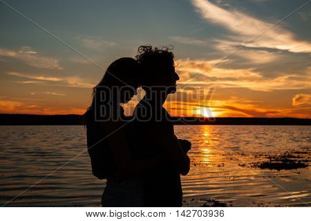 Silhouette of happy young couple hugging near the sea on sunset