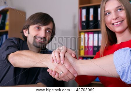 Three Business People Men and Woman joining Hands reaching Deal after challenging Negotiations Office Background Casual Clothing Focus on Hands