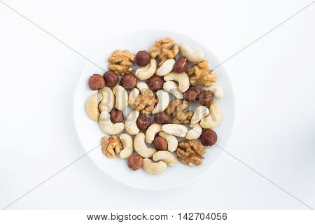 A mixture of cashews walnuts and hazelnuts on a white plate