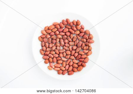 Crude red peanuts on a plate on a white background