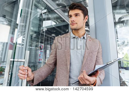 Attractive young businessman holding clipboard and entering the door in office
