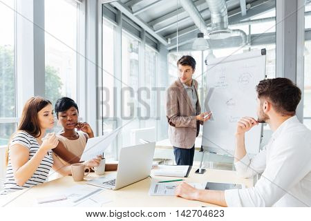 Handsome young businessman making presentation using flipchart in office