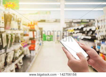 Hand with smart phone white screen on blurred shopping mall background