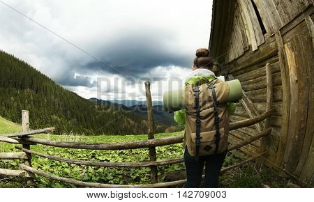 Female tourist beside house in mountains