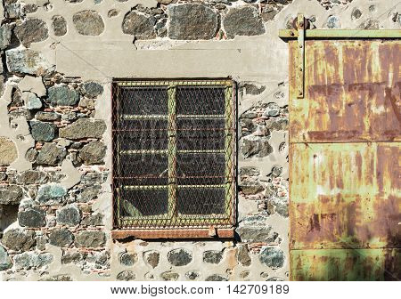 Old closed green metal window and door on a stone wall of a deserted building.