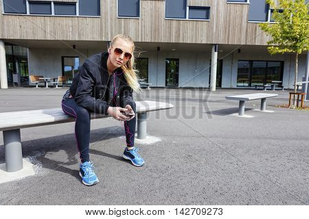 Beautiful woman with sunglasses sits on a bench in the city wearing a jacket and workout outfit. Listens to music and using smart phone.
