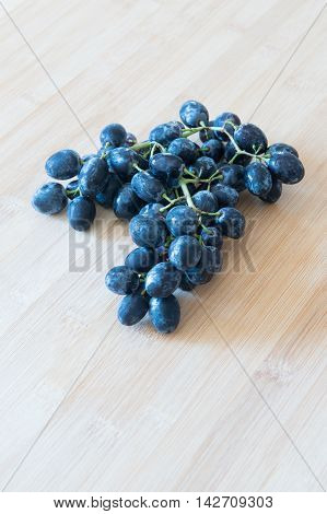 Branch of healthy red grape fruits for producing wine on a wooden board.