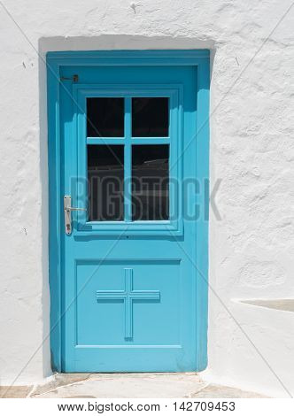 Blue traditional closed church door on a white wall from the Greek islands if Greece