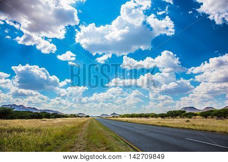 Along the road low trees and yellowed grass. Fluffy clouds over the savannah. The good asphalt highway in Namibia