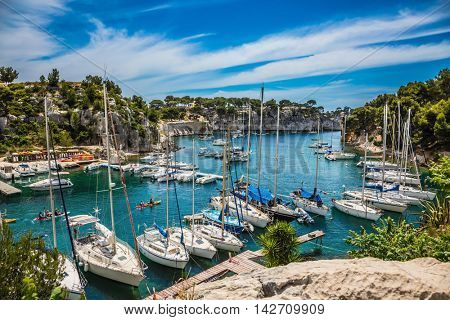 Graceful sailing yachts in the sea fjord. The picturesque gulf with turquoise water at coast of the Mediterranean Sea. National park of Calanques in Provence, between Marseille and Kassis