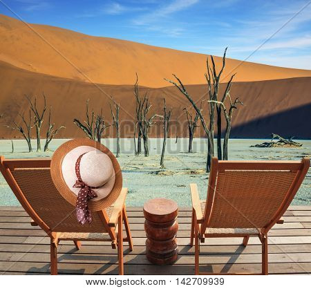 Two wooden folding chairs - deck chairs on a wooden platform. Ecotourism in Namib-Naukluft National Park, Namibia. The bottom of dried lake Deadvlei, with dry trees