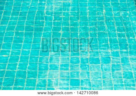 Blue-green swimming pool bottom with water wave texture.