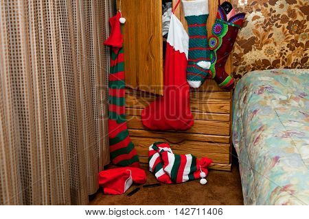 Six Christmas stocking hang on a dresser ready to be discoverd on Christmas morning. They are huge and most are stuffed.