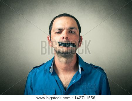 portrait of man with the taped mouth