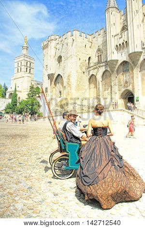 AVIGNON, FRANCE - JULY 19 2014: actors in historical costumes advertising their performance on place in front of the Papal Palace during famous theatre festival from July 4 to 27 2014 in Avignon south of France.