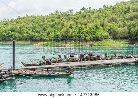 SURAT THANI THAILAND - MAY 30: Boats are docked at the marina in Ratchaprapha dam with beautiful green water on May 30 2016 in Surat Thani Thailand.