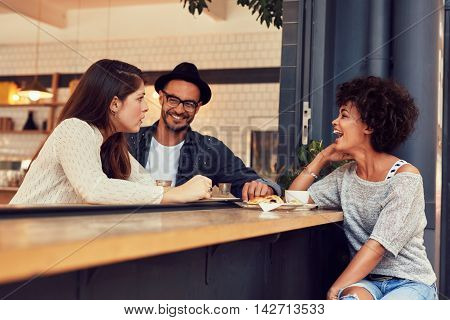 Portrait of a young group of friends talking in a cafe. Young man and women sitting at cafe table and talking.