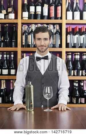 Confident Bartender With White Wine Standing At Counter