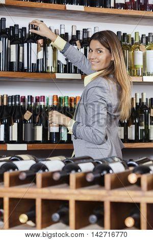 Woman Removing Wine Bottle From Shelf In Shop